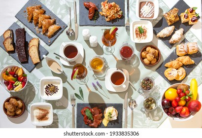 Impressive breakfast set up on a clothed table with traditional Mediterranean delicacies served on plates and plateau with coffee, tea, juices and marmalade.