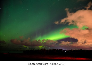 Impressive bright northern lights behind orange clouds in autumn. Natural light show - a phenomenon caused by particles flying from the sun during a magnetic storm. October 2018, Oulu, Finland.