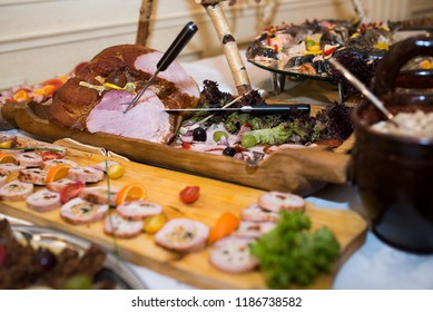Impressive buffet woodentable in a wedding hall with meat, cheese, and traditional Polish food lard fat, pig, turkey