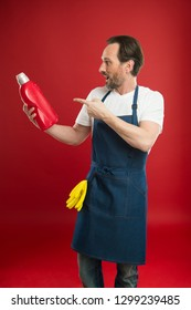 Impressive cleaning power. Mature man pointing at detergent bottle. Senior man in apron ready for doing laundry. Eldery household worker presenting laundry detergent. Household laundering.
