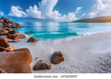 Impressive clouds above crystal clear ocean and beautiful tropical beach. Seychelles Grand Anse, La Digue, Seychelles