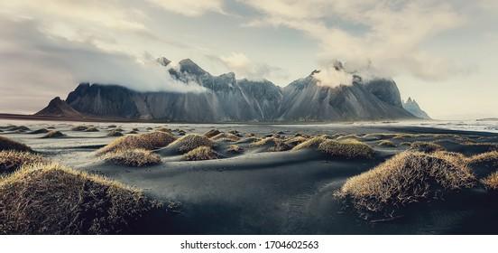 Impressive Colorful Seascape of Iceland. Wonderful picturesque Scene  near Stokksnes cape and Vestrahorn Mountain, Black sand dunes under sunlight on foreground.