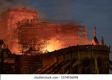 Impressive fire in Notre-Dame de Paris cathedral at night on April 15, 2019, France. View from the back with scaffold structure in fire.
