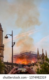 Impressive fire in Notre-Dame de Paris cathedral at night on April 15, 2019, France. View from the side with scaffold structure in fire, large smoke cloud, and a person taking picture with phone