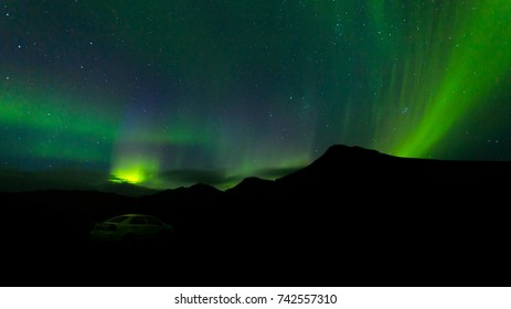 Impressive green Aurora Borealis (Northern lights) in Iceland.Northern pole phenomenon.Natural light show above arctic circle mountains.Visible polar light,magnetic particle collision display