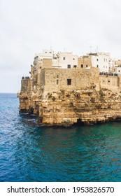 Impressive and historic White- washed Puglian Town perched atop limestones cliffs above azure water. Polignano Al Mare, Puglia