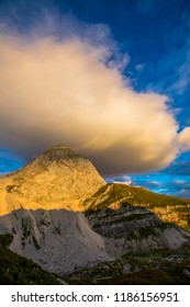 Impressive Mangart mountain in the sunset. Round cloud over the peak of a mountain. Julian alps in Slovenia. Mountain beak in the sunset. Famous rockface for climbing.