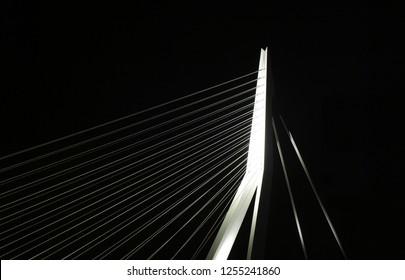 the impressive modern Erasmusbridge in Rotterdam illuminated during nighttime