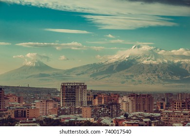 Impressive mount Ararat background. Yerevan cityscape. Travel to Armenia. Tourism industry. Cloudy sky. Armenian architecture. City tour. Urban landscape. Sightseeing concept. Copy space. Multistory