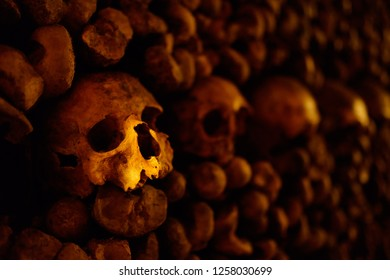 Impressive number of human skulls and bones in dark, spooky ambiance. Remains of people buried underground in catacombs.