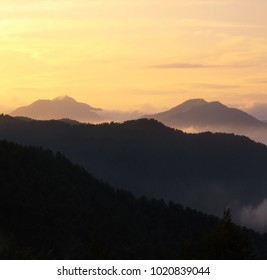impressive photo of mountains, colorful summer scenery, gold yellow sky on horizon