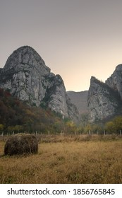 Impressive pointy mountain cliffs at the misty entrance of Jerma river canyon and foreground hay bale on a field - Shutterstock ID 1856765845