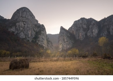 Impressive pointy mountain cliffs at the misty entrance of Jerma river canyon and foreground hay bale on a field - Shutterstock ID 1857449596