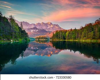 Impressive summer sunrise on the Eibsee lake with Zugspitze mountain range. Splendid outdoor scene in German Alps, Bavaria, Garmisch-Partenkirchen village location, Germany, Europe.
