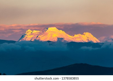 Impressive view of the Antisana volcano from the city of Quito in reddish tones, at sunset.