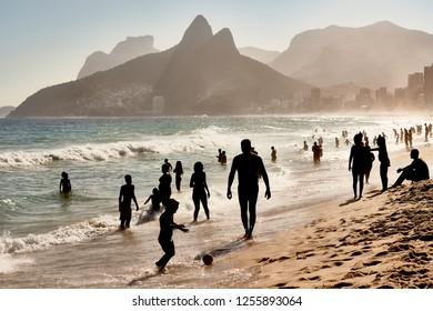 Impressive View of Crowded Beach with Silhouettes of Brazilian People and Two Brothers Mountain in a Sunny Summer Season Day