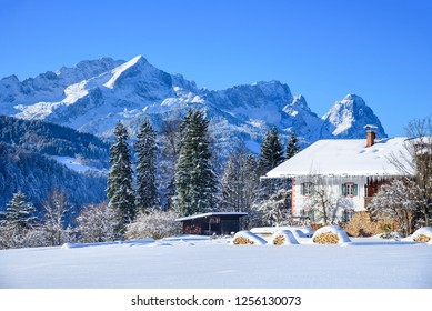 impressive view to mountain range of Zugspitze with farm house in foreground