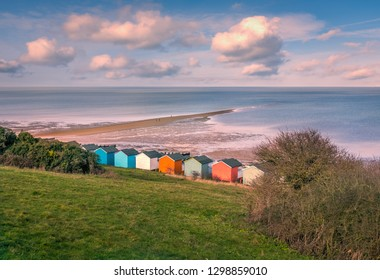 Impressive winter clouds in a cool blue sky over the beach huts and natural spit of land that stretches out to sea on the beach in Tankerton, Whitstable, Kent, UK.