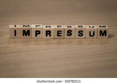 impressum (german imprint) written in wooden cubes on a desk