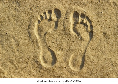 imprint of man's foot on the sand on the beach.