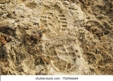 Imprint of a man's foot in shoes on wet sand