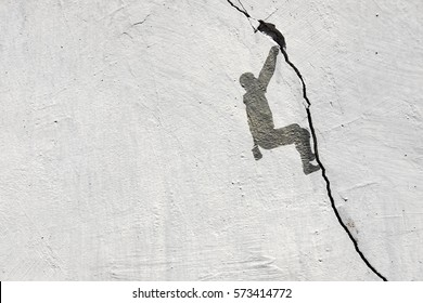 Imprint of a rock climber scaling a crack in a rugged concrete wall.