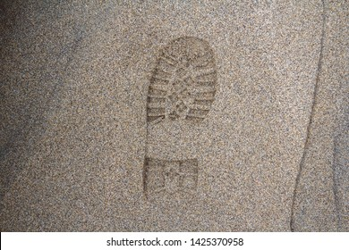 Imprint of the shoe on mud with copy space, Footprint in the dirt, Foot step on sand, background texture. Top view.