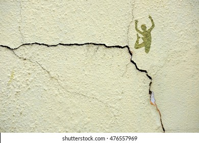 Imprint of a silhouette of a boy jumping off the edge of a crack on a concrete wall, for the concept: Crack under pressure.