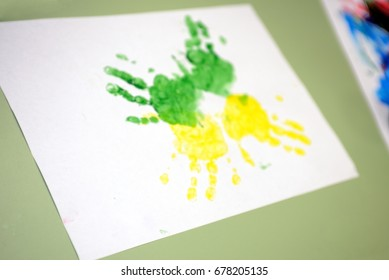 Imprint of watercolor paint on a child's hand on paper