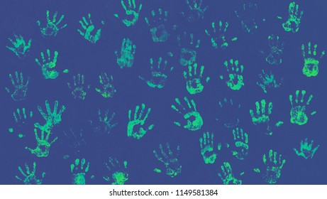 Imprints of human palms of luminous phosphor paint  on blue background for your creative art-project. Abstract wallpaper from various of handprints in a green acid tones.