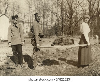 Imprisoned family of Russian Czar Nicholas II gardening at Tsarskoe-Selo. 1917. Grand Duchess Tatiana, daughter of the Czar, transporting sod on a stretcher with the aid of a soldier.