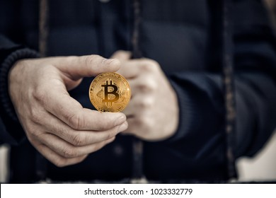 Imprisoned hacker holds coin bitcoin and prison lattice. Concept arrest, fraud and deception with crypto currency and mining.