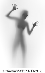 Imprisoned woman behind a glass wall, shouts. Face, silhouette, hands.