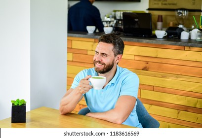 Improve overall health. Take moment to care about yourself. Coffee drinkers live longer. Man bearded guy drinks cappuccino wooden table cafe. Cafe visitor happy smiling face enjoy coffee drink.