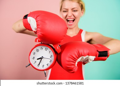Improve yourself. Overcome harmful habits. Time for training. Get used to personal regime. Girl athlete boxing gloves and alarm clock. Sport lifestyle and healthy regime. Habits and regime concept.