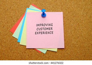 IMPROVING CUSTOMER EXPERIENCE written on color sticker notes over cork board background.