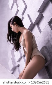 Improving posing skills. Eye-catching beautiful dark-haired beaming supermodel with nice make-up improving posing skills while studio photo shooting