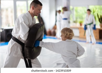 Improving strength. Curly blonde-haired boy loving martial arts improving his strength