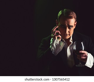 Improvising. Comedian man with mime makeup hold wine glass. Drama theatre actor miming. Performance art and silen comedy. Mime artist perform on stage. Stage actor pantomime drinking wine, copy space.