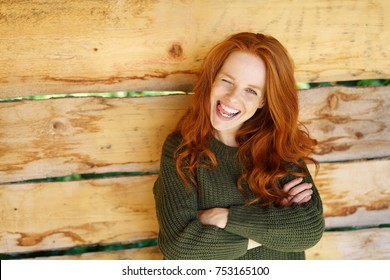 Impudent young woman winking playfully at camera with a mischievous grin and folded arms over a rustic wood background with copy space
