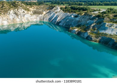 Inactive gypsum quarry. In the quarry is a lake with blue water.