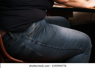 Inactive lifestyle, insufficient physical activity, sedentary work, sitting disease, weight gain. Overweight woman sitting on chair, close up