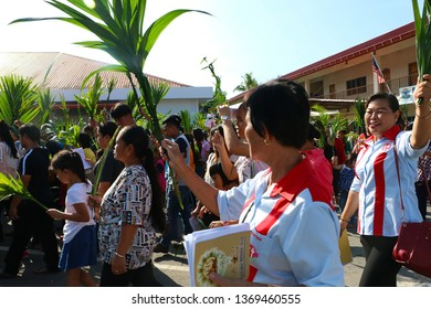 INANAM, KOTA KINABALU, SABAH- APRIL 14, 2019: Some 1000 St Catherine's church parishioners waving palm leaves as they sing 'Hosanna' during a procession to celebrate Palm Sunday