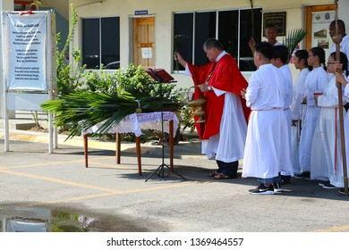 INANAM, KOTA KINABALU, SABAH- APRIL 14, 2019: Catholic priest blesses palm branches as parishioners lift a palm frond during a procession to celebrate Palm Sunday