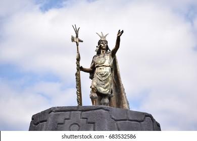 Inca statue standing high at a square in Cuzco Peru.