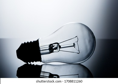 Incandescent lamp lying on a table on a gray gradient background with reflection