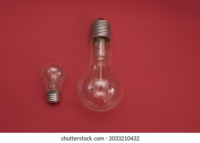 incandescent lamps. large and small incandescent bulbs on a red background. copy space