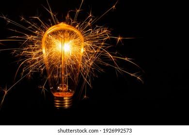 Incandescent light bulb with emitting sparks on black background