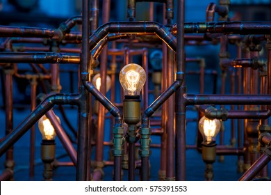 Incandescent light bulbs between pipes