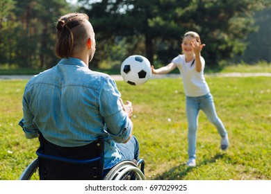 Incapacitated young man catching ball thrown by daughter